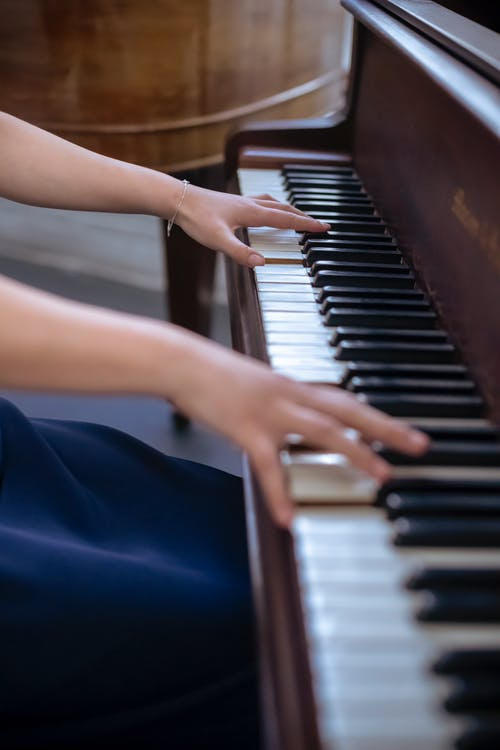 Crop skilled woman playing piano