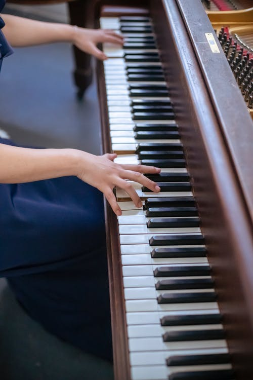 Side view of unrecognizable skilled female musician in elegant wear playing melody on piano while rehearsing and performing in light room