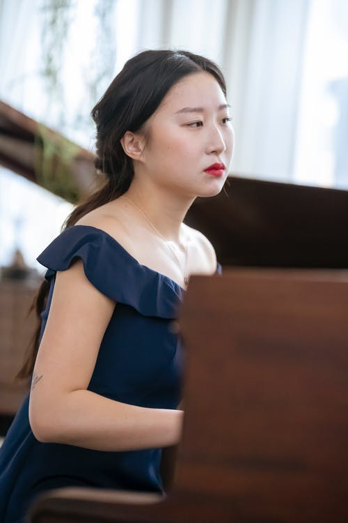 Side view of serious Asian female musician wearing classy dress playing piano while rehearsing in room near windows at home