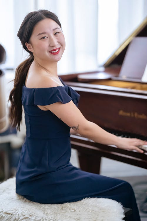 Smiling Asian female musician in elegant outfit looking at camera while performing melody on piano during rehearsal in light room