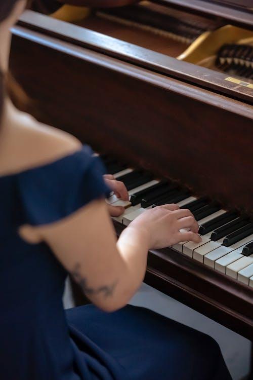 Crop woman in elegant wear playing piano