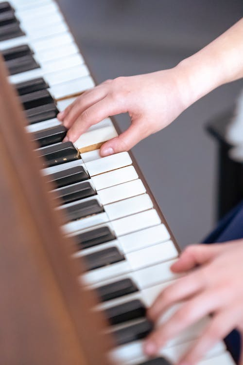 From above of anonymous female musician playing melody on keyboard of piano during music lesson in light room at home