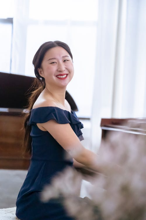 Smiling Asian woman in elegant dress playing piano