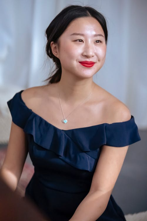 High angle of charming positive ethnic female with red lips wearing elegant dress and necklace looking away