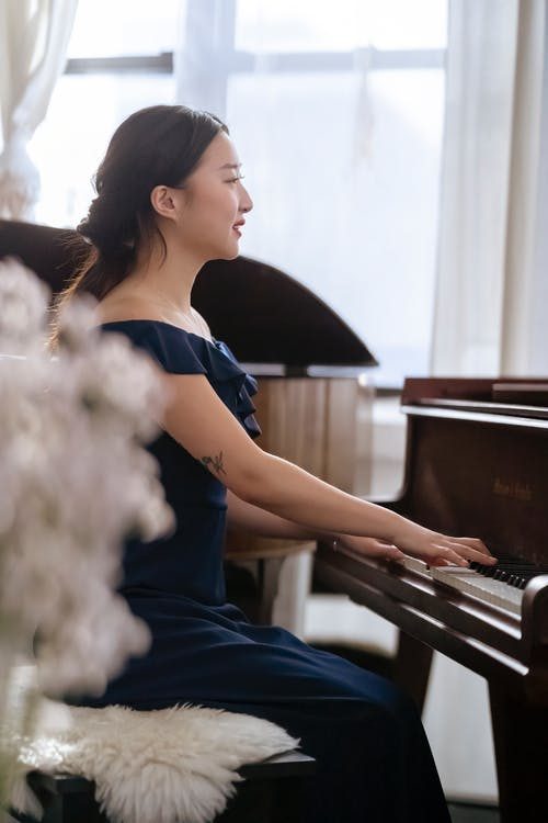 Side view of ethnic woman in elegant dress sitting on chair and playing piano while practicing melody