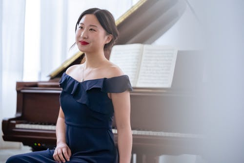 Elegant Asian female musician sitting near piano