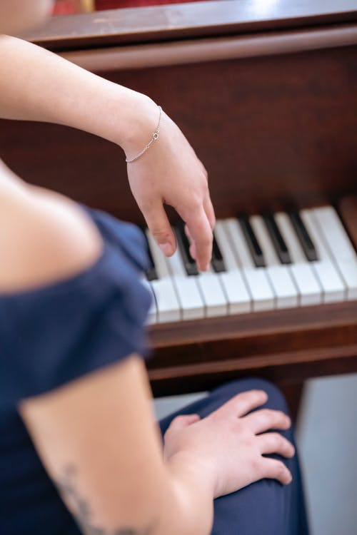 High angle back view of crop anonymous female musician sitting near piano for practicing classical music