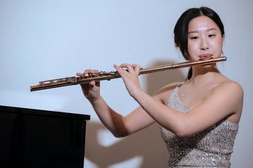 Ethnic woman in dress playing flute at concert