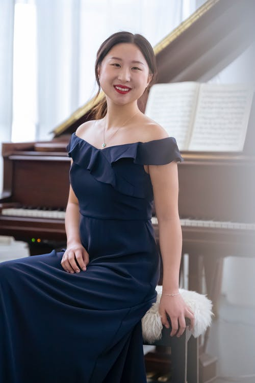 Elegant Asian woman with toothy smile sitting on chair near musical instrument before performance and looking at camera