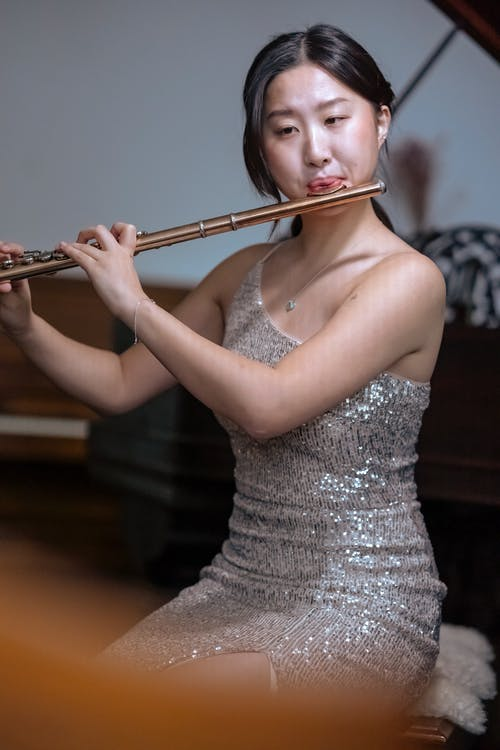 Asian woman playing flute near piano for event