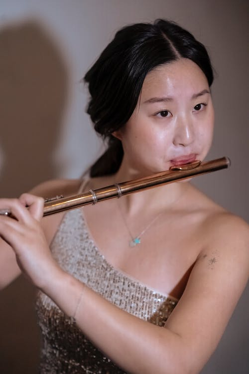 Ethnic female wearing dress playing flute at while at spotlight on stage at concert