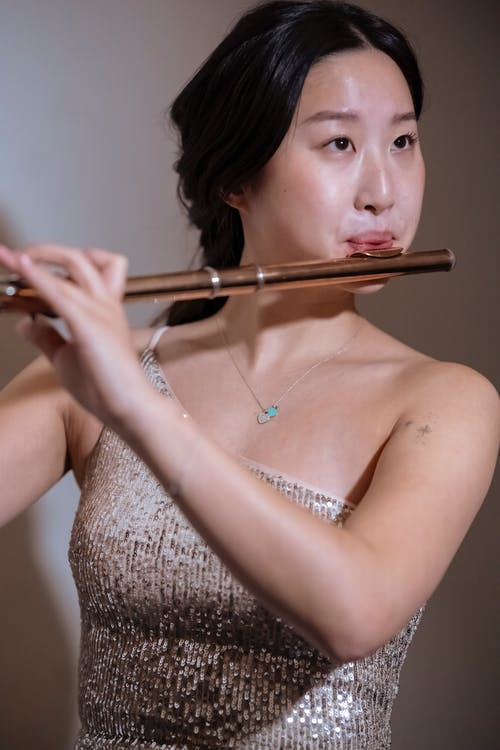Focused Asian woman playing acoustic instrument