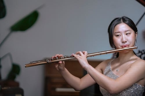 Talented ethnic female musician in shiny dress playing classic instrument flute while having live performance in concert hall