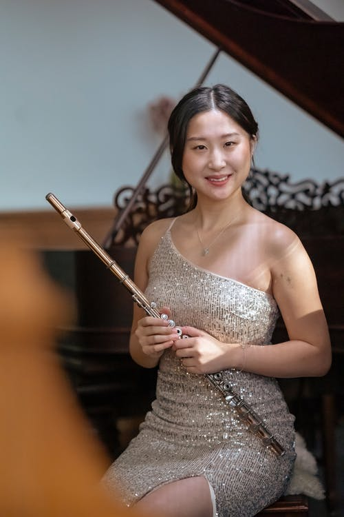 Smiling Asian woman with flute sitting on stage