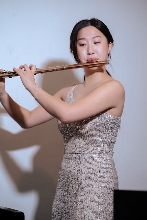 Elegant Asian female musician in elegant dress standing on stage at spotlight and playing flute during performance