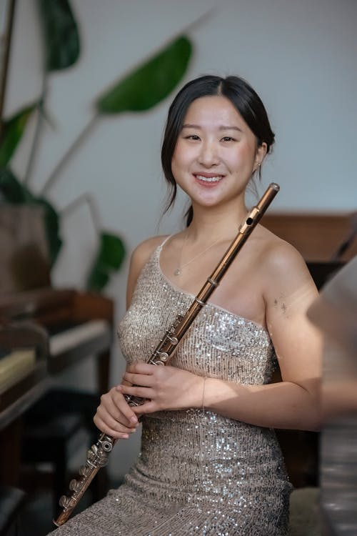 Charming smiling ethnic female musician in dress with flute sitting near piano and looking at camera