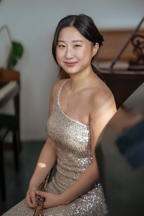 Smiling Asian woman with flute at event