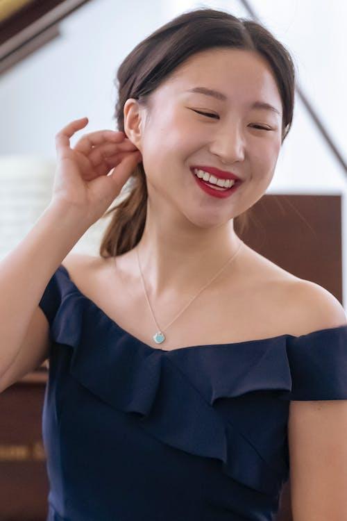 Smiling Asian woman sitting near piano