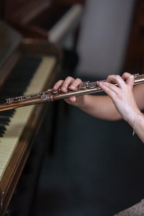 Crop woman playing flute near piano