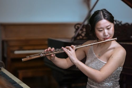Talented Asian female musician in elegant dress playing melody on flute while sitting near piano in modern studio on blurred background