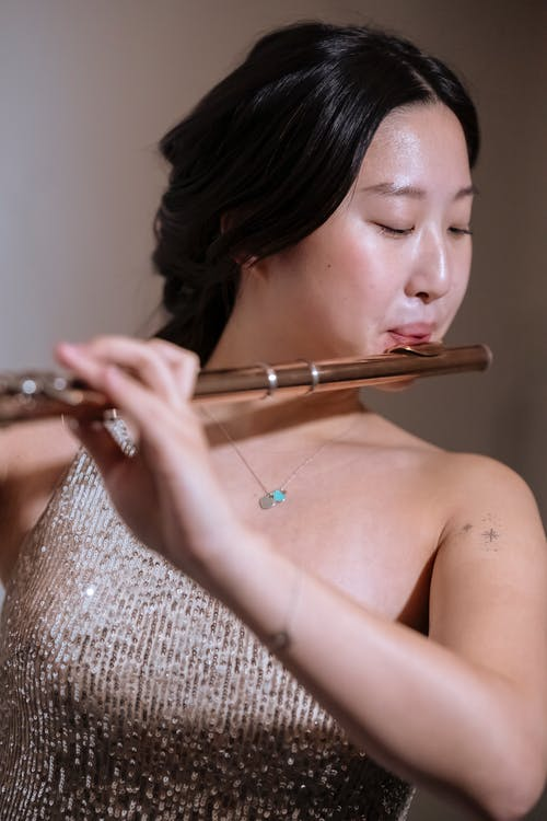 Focused Asian woman practicing melody flute