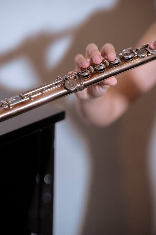 Faceless professional musician playing melody on long flute while standing near white wall during rehearsal in studio on blurred background