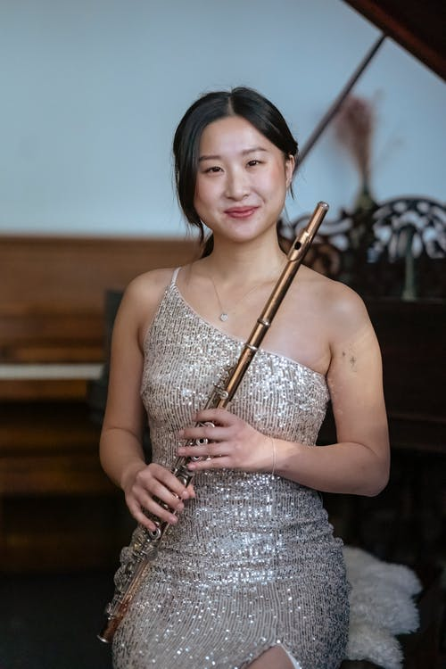 Positive Asian female musician in elegant dress smiling and looking at camera while sitting near piano with flute in room