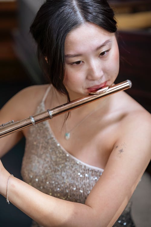 Focused Asian woman playing flute