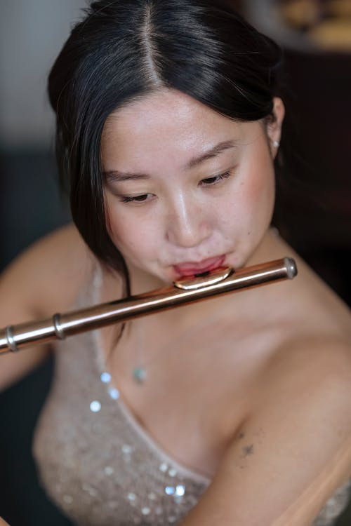 Focused talented Asian female with black hair in dress playing on flute while rehearsing in light room on blurred background