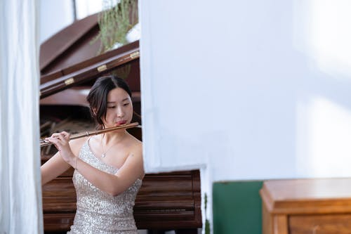 Focused Asian female musician in fancy outfit playing melody on flute while sitting near piano in light room during rehearsal