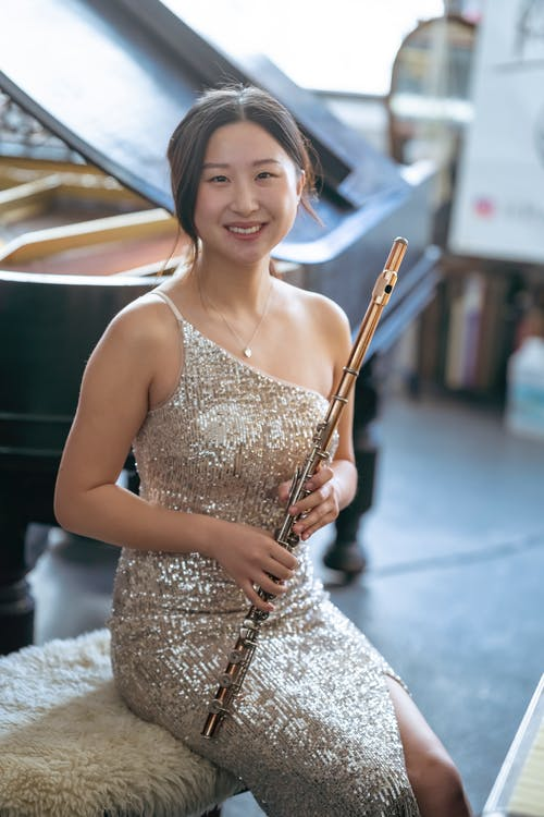 Delighted Asian musician with flute
