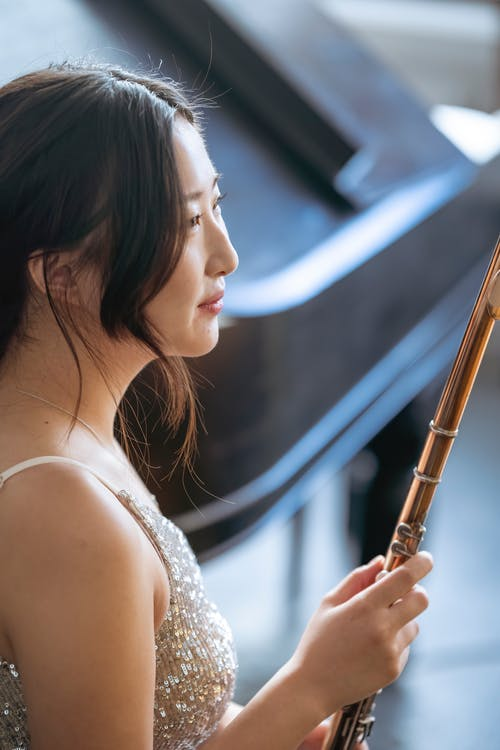 Side view of content Asian female with dark hair in elegant dress sitting near piano with flute in hand on blurred background