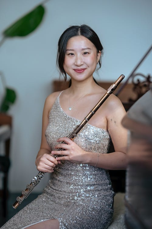 Charming Asian female player with black hair wearing fancy dress looking at camera while sitting in light room during rehearsal