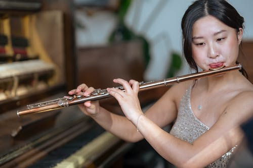 Talented Asian female player in fancy dress playing melody on flute while sitting near piano during rehearsal on blurred background