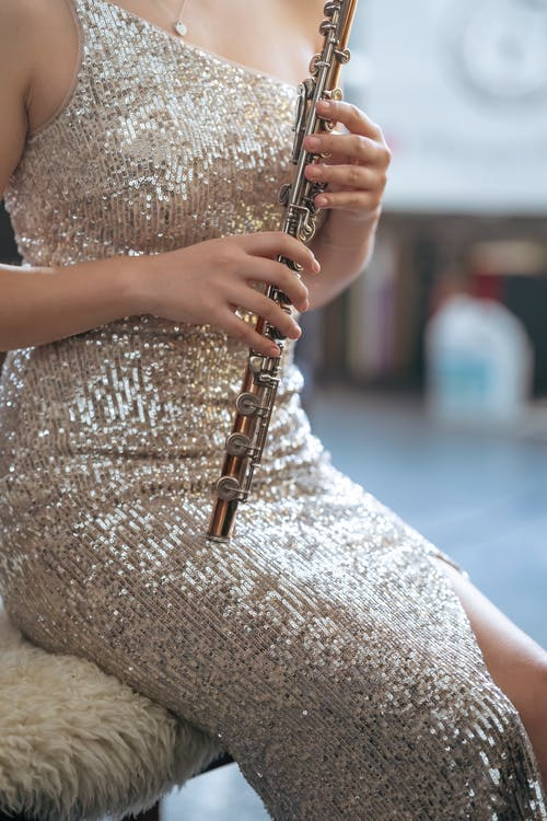 Crop woman in dress playing flute
