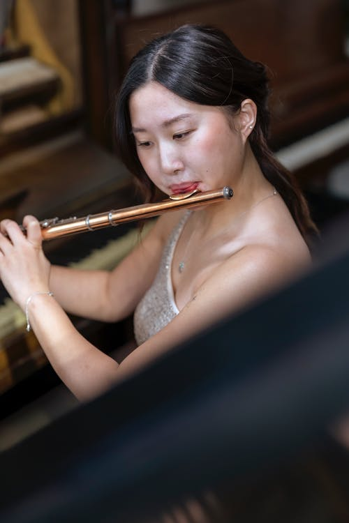 Serious Asian woman playing flute