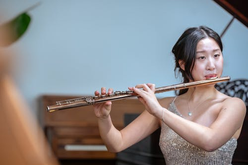 Concentrated Asian female musician in fancy dress playing melody on flute while sitting near piano in light room on blurred background