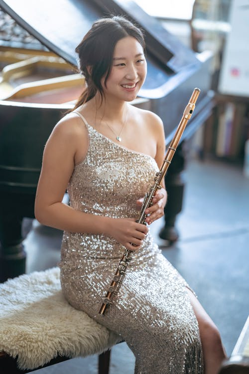 Attractive Asian female player wearing stylish dress sitting on chair near piano in light room on blurred background during rehearsal