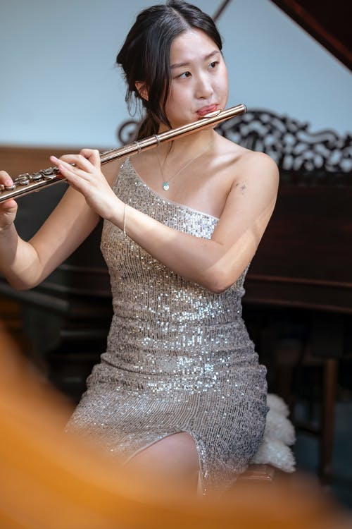 Skilled Asian female musician in trendy dress looking away while sitting near piano and playing flute in light room during rehearsal