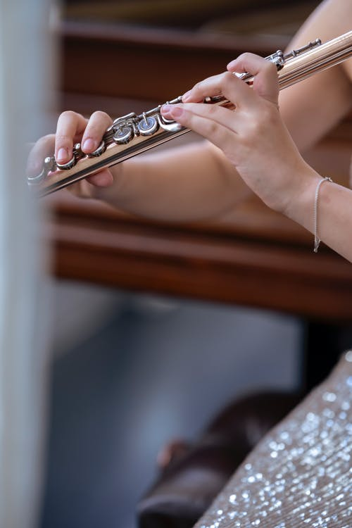 Young female musician in elegant dress sitting near piano and playing flute in concert hall