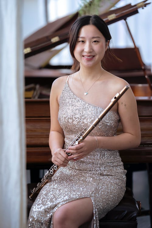 Smiling Asian woman in elegant dress with flute
