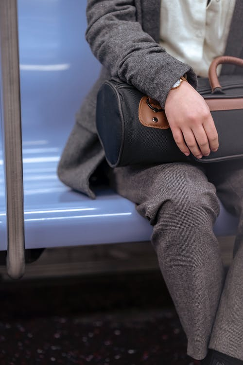 Crop unrecognizable female in trendy coat and trousers sitting on seat in train and holding bag