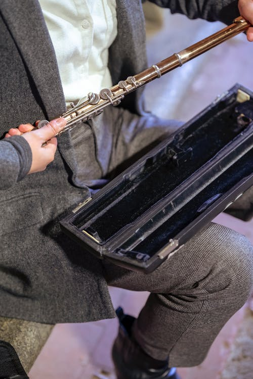 Woman taking flute from case for music performance