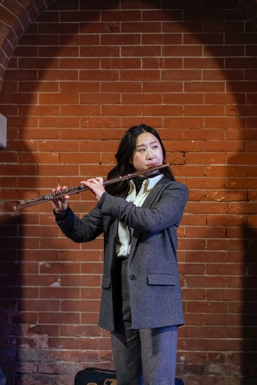 Elegant Asian female musician standing on street against brick wall and playing flute