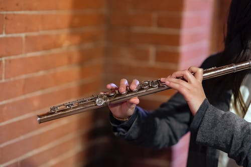 Crop unrecognizable female musician pressing keys on flute while performing melody on street against brick wall