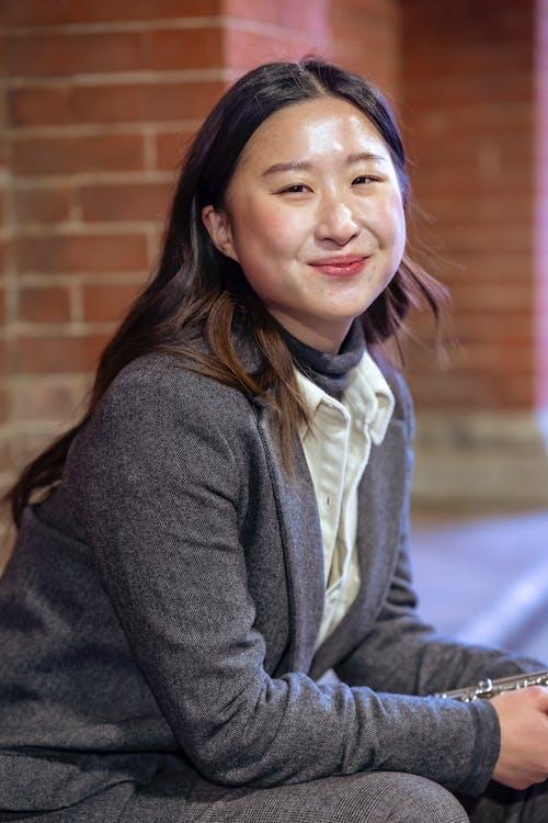 Positive Asian woman sitting on street