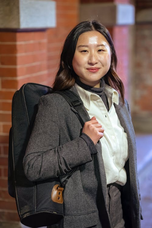 Smiling ethnic woman with backpack on street