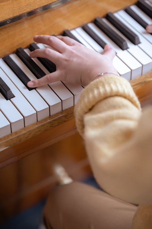 From above of crop anonymous female musician playing piano while practicing classical music