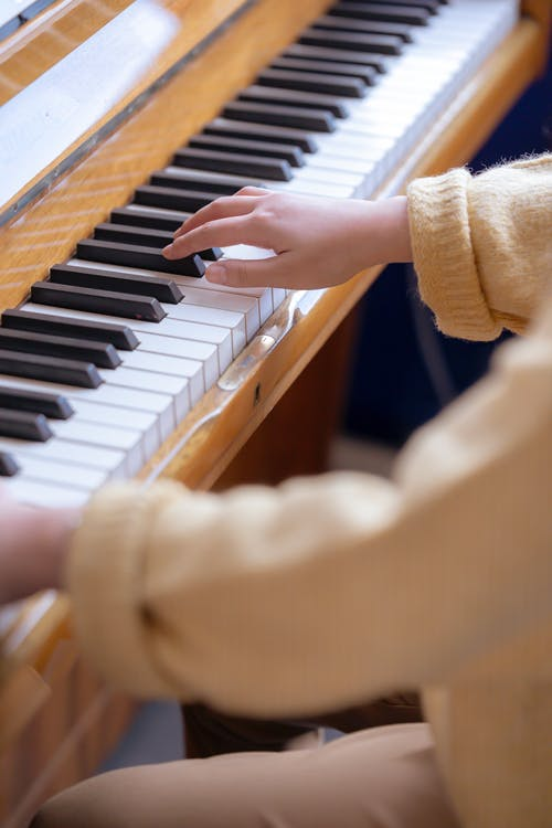 High angle of crop anonymous female musician practicing music on piano at daytime