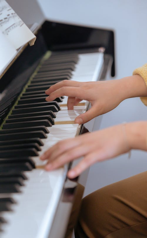 Crop anonymous female pianist pressing keys and practicing melody on piano during rehearsal